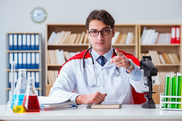 Superhelddoktor, der im krankenhauslabor arbeitet Premium Fotos
