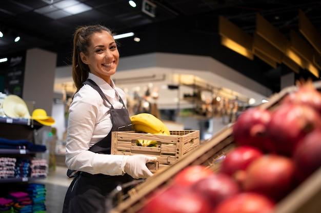 Supermarktarbeiter, der die obstabteilung mit lebensmitteln versorgt Kostenlose Fotos