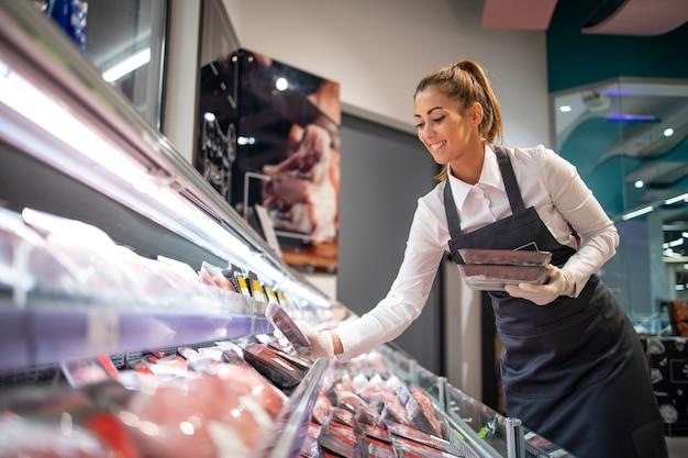 Supermarktarbeiter organisiert position in der fleischabteilung Kostenlose Fotos