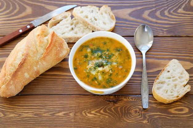 Suppe in einer platte mit scheiben brot auf einem holztisch. vegetarische, vegane küche. Premium Fotos