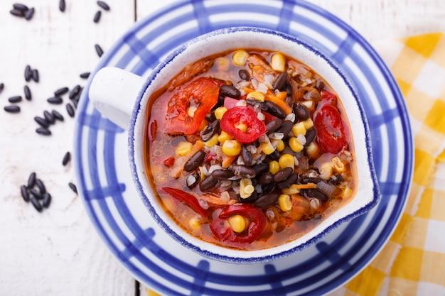 Suppe mit schwarzen bohnen, buchweizen, paprika und mais. Premium Fotos