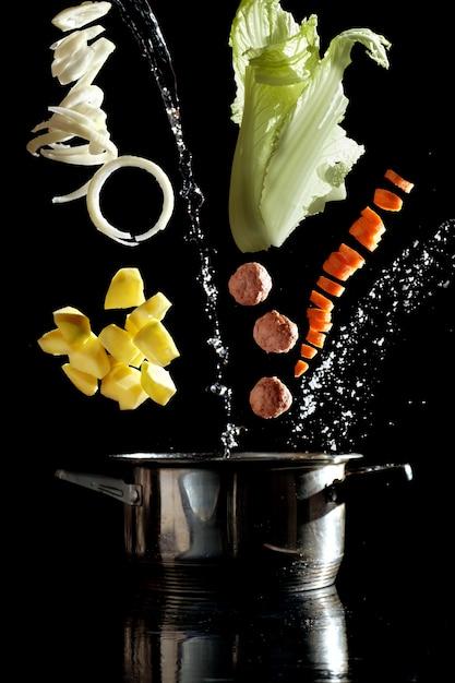 Suppenzubereitung, gemüse schwebend in der luft über der suppenpfanne Premium Fotos