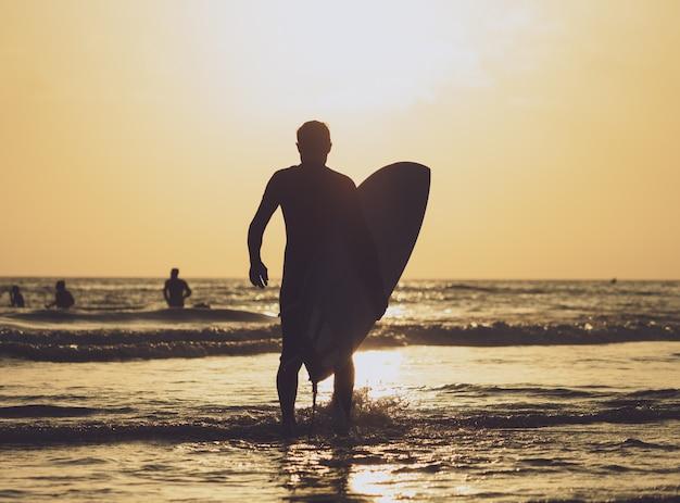 Surfer, der das brett zum meer zur sonnenuntergangzeit durchführt Premium Fotos
