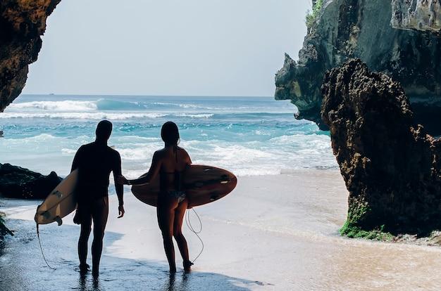 Surfer, die ins meer kommen und bereit sind, auf den wellen zu surfen. kuta beach, bali. Premium Fotos