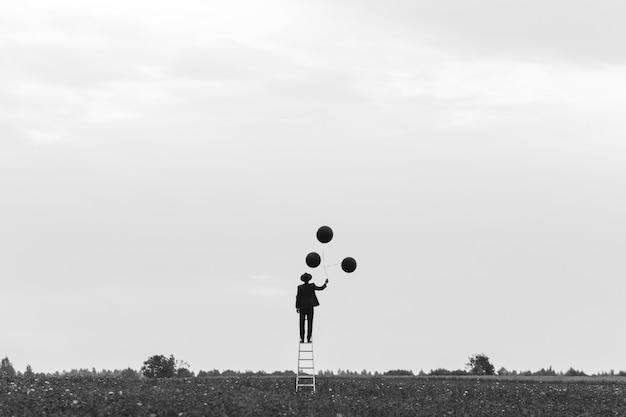 Surreale silhouette eines mannes in einem anzug, der auf der treppe in einem feld mit luftballons steht. konzept der freiheit Premium Fotos