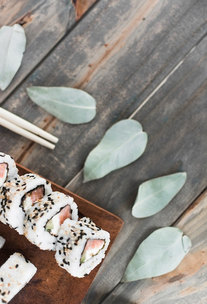 Sushi auf hölzernem behälter mit blättern und essstäbchen auf holztisch Kostenlose Fotos