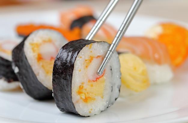 Sushi halten stäbchen und in die sauce getaucht. Premium Fotos