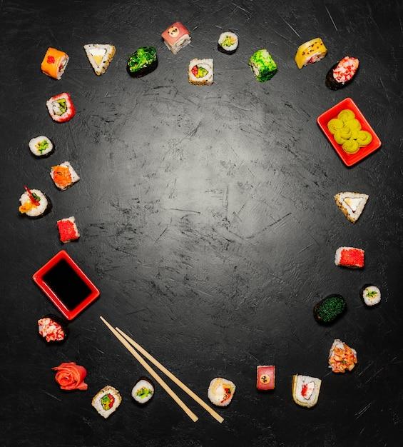 Sushi-hintergrund. draufsicht von japanischen sushi und von essstäbchen auf schwarzem hintergrund Kostenlose Fotos