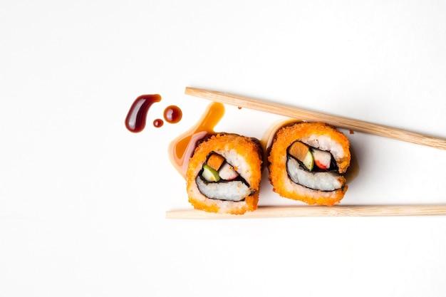 Sushi, japanisches lebensmittel, kalifornien rollen mit essstäbchen und soße auf weißem hintergrund. Premium Fotos