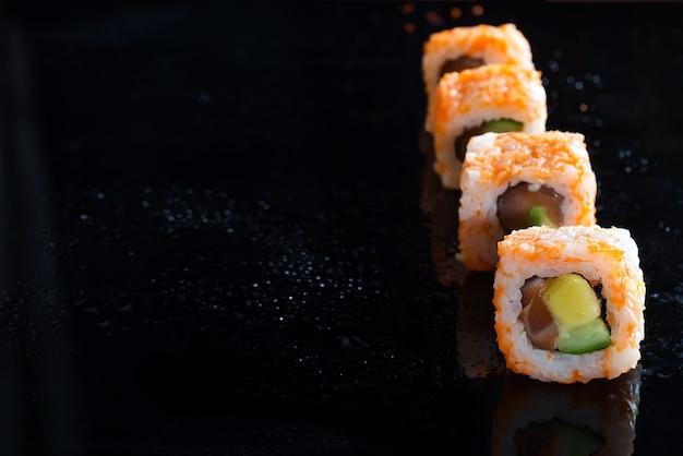 Sushi-rolle kaliforniens maki gemacht vom krebsfleisch, avocado, gurke auf schwarzem glashintergrund Premium Fotos