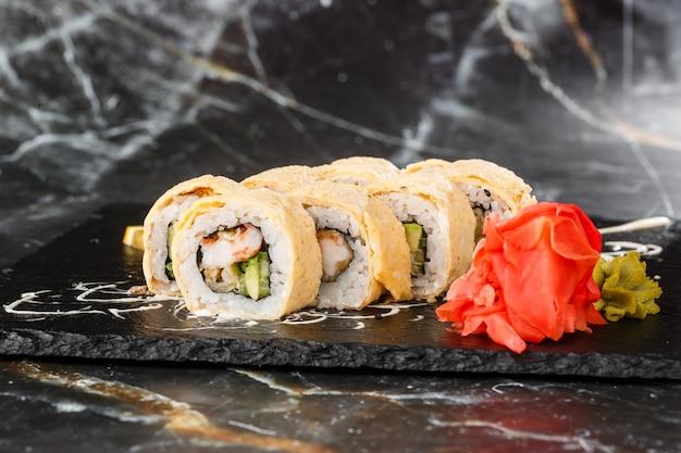Sushi-rollen mit avocado, aal, gurke und frischkäse innen auf schwarzem schiefer lokalisiert auf schwarzem marmorhintergrund. kalifornische brötchen auf omelett-sushi-menü. horizontales foto. Premium Fotos
