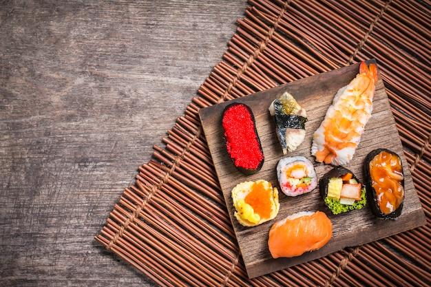 Sushi set sashimi und sushirollen auf holzschiefer serviert Premium Fotos