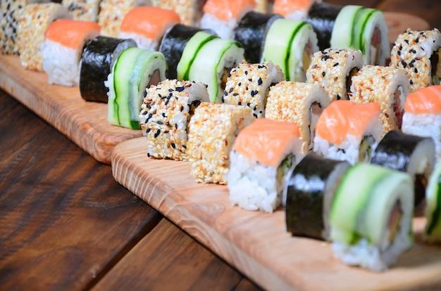 Sushi-set von mehreren rollen befindet sich auf einem holzschnitt Premium Fotos