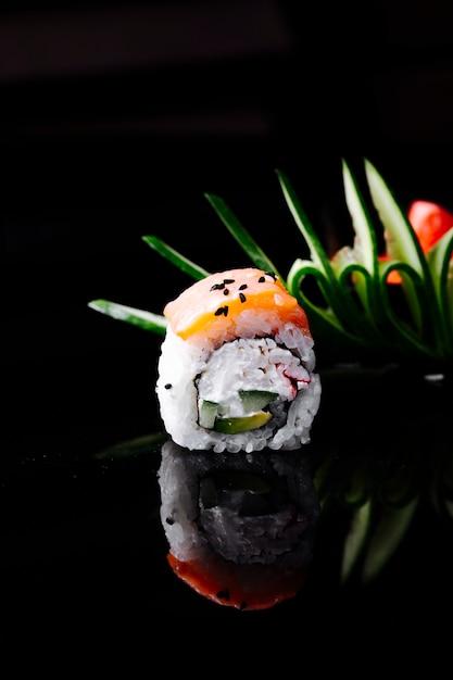 Sushirolle mit lachs- und frischkäse im dunklen raum. Kostenlose Fotos