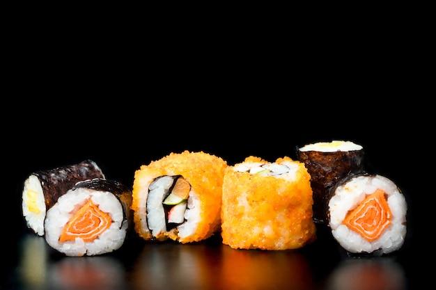 Sushirollen auf schwarzem hintergrund, japanisches lebensmittel. Premium Fotos