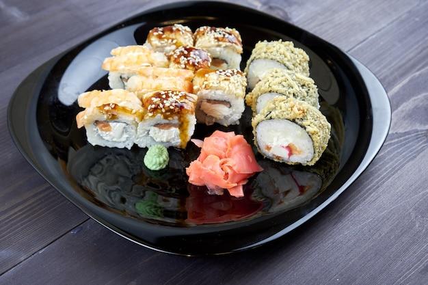 Sushirollen mit ingwer und wasabi auf einem schwarzblech Premium Fotos