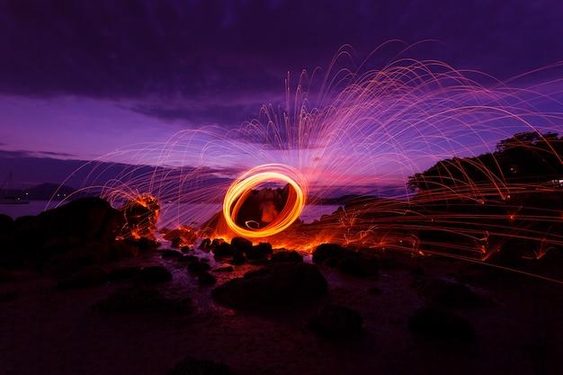 Swing fire swirl stahlwolle licht fotografie über den stein mit reflex im wasser schönes licht in der sonnenaufgangs- oder sonnenuntergangszeit, lange belichtungsgeschwindigkeit bewegungsstil Premium Fotos