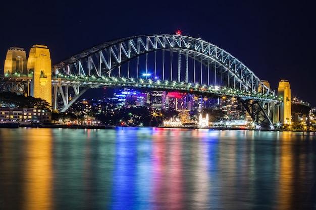 Sydney habour-brücke in sydney australia nachts mit einem stadtbild im hintergrund. Premium Fotos