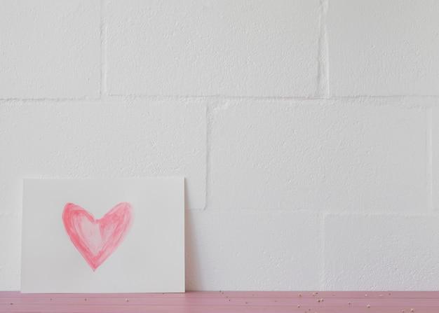 Symbol des herzens auf weißbuch nahe wand Kostenlose Fotos