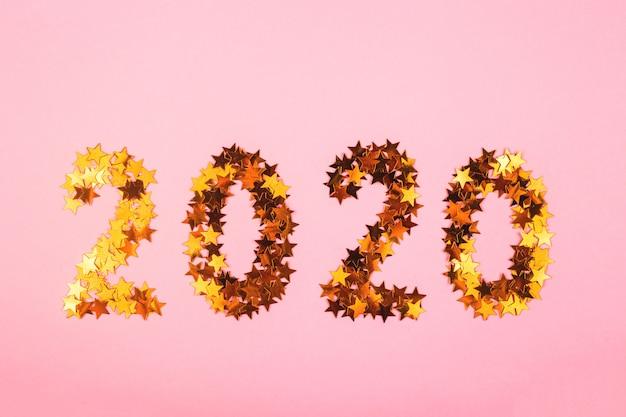Symbol des neuen jahres 2020 von goldkonfettis auf rosa hintergrund. Premium Fotos