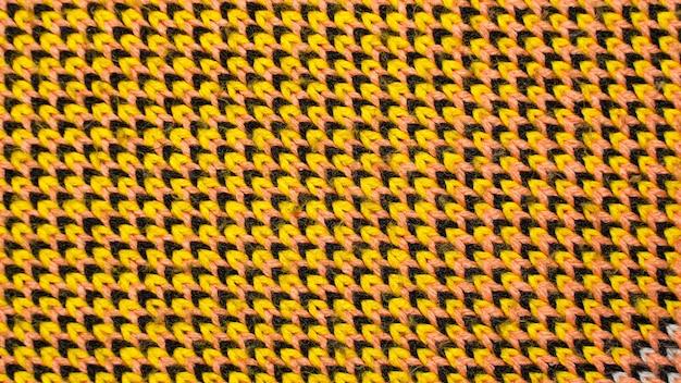 Synthetische strickware mit musterelementen aus gelben, schwarzen und roten garnen in nahaufnahme. mehrfarbig gemusterte strickstruktur. hintergrund Premium Fotos