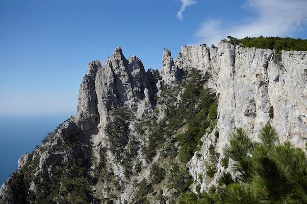 Szenische ansicht des erstaunlichen berges ai-petri gegen blauen himmel und den hintergrund des schwarzen meeres. berge, wandern, abenteuer, reisen, touristenattraktion, landschafts- und höhenkonzept. krim, russland. Kostenlose Fotos