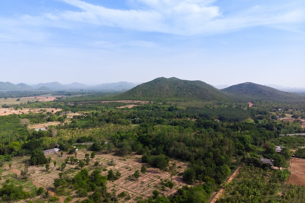 Szenische landschaft der brummenschussvogelperspektive des landwirtschaftsbauernhofes gegen berg und naturwald Premium Fotos