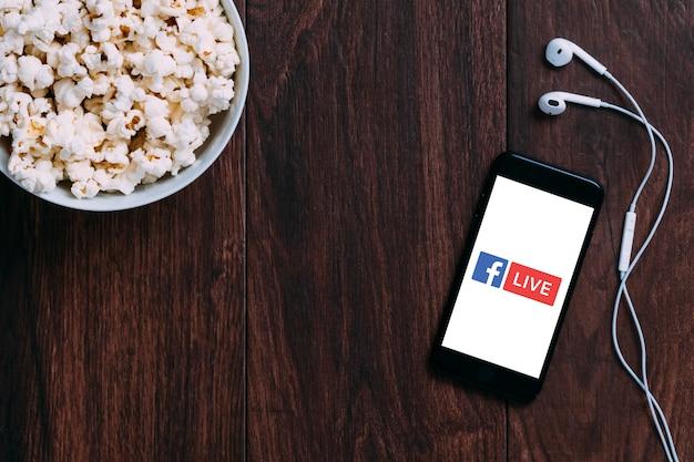 Tabelle mit popcorn-flasche und facebook live-logo auf apple iphone und kopfhörer. Premium Fotos