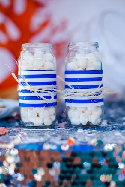 Tabelle mit seedekor und platte mit bonbons, süßigkeiten, plätzchen und verziert gläser mit eibisch Premium Fotos