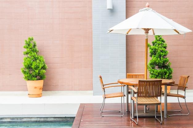 Tabelle und stuhl mit patio des weißen regenschirmes im freien Kostenlose Fotos
