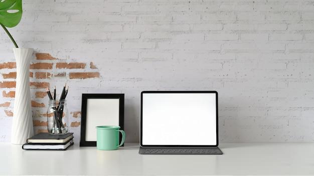 Tablet des leeren bildschirms des modells auf weißem hölzernem schreibtisch und versorgungen Premium Fotos