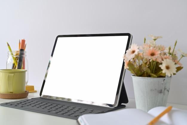 Tablet des leeren bildschirms des modells mit tastatur auf hauptstudioarbeitsplatz Premium Fotos