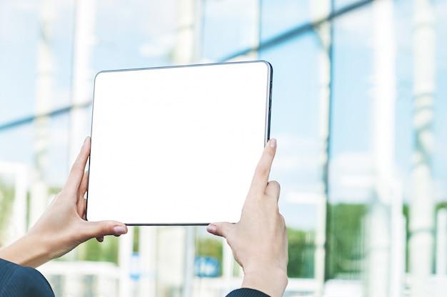 Tablet in den weiblichen händen, vor dem hintergrund des glasgeschäftszentrums. Premium Fotos