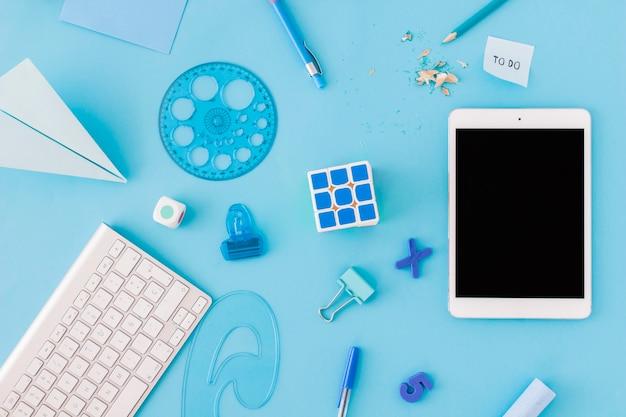 Tablet in der nähe von schulzeug und tastatur Kostenlose Fotos