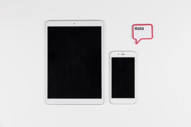 Tablet in der nähe von smartphone und rahmen mit hola inschrift Kostenlose Fotos