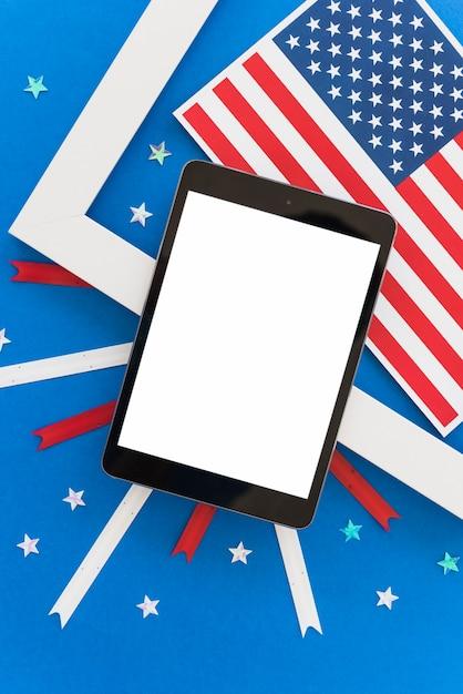 Tablet- und feiertagsdekoration des unabhängigkeitstags auf blauem hintergrund Kostenlose Fotos