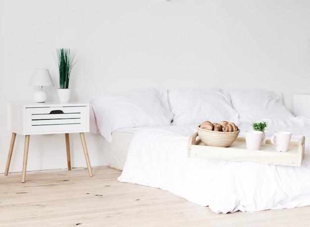 Tablett mit frühstück auf dem bett im hellen schlafzimmer Kostenlose Fotos