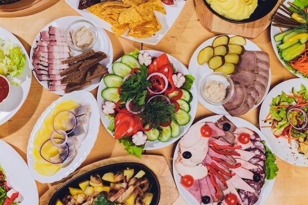 Tablett mit leckeren salami, stücke schinken, wurst und salat. fleischplatte mit auswahl auf dem tisch. Premium Fotos