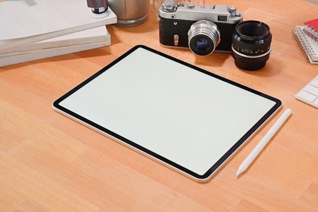 Tablette des leeren bildschirms auf hölzernem stilvollem schreibtisch mit kreativem fotografenversorgungen und kopienraum Premium Fotos