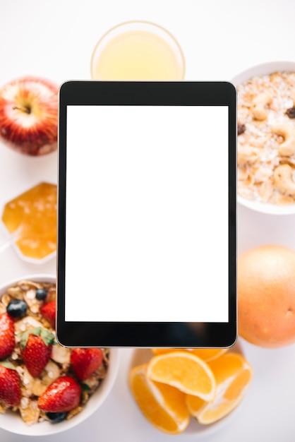 Tablette mit leerem bildschirm über haferflocken und früchten Kostenlose Fotos