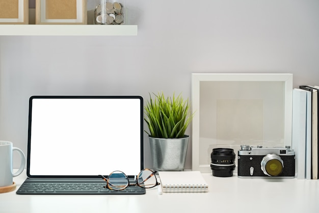 Tablette, plakat, bücher und weinlesekamera des modells des leeren bildschirms auf arbeitsplatz Premium Fotos