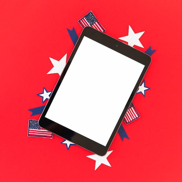 Tablette und symbole von amerika auf roter oberfläche Kostenlose Fotos