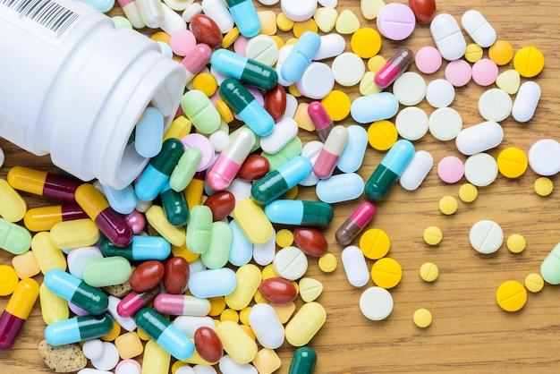 Tablettenfläschchen, das an pillen verschüttet, um hölzern aufzutauchen Premium Fotos