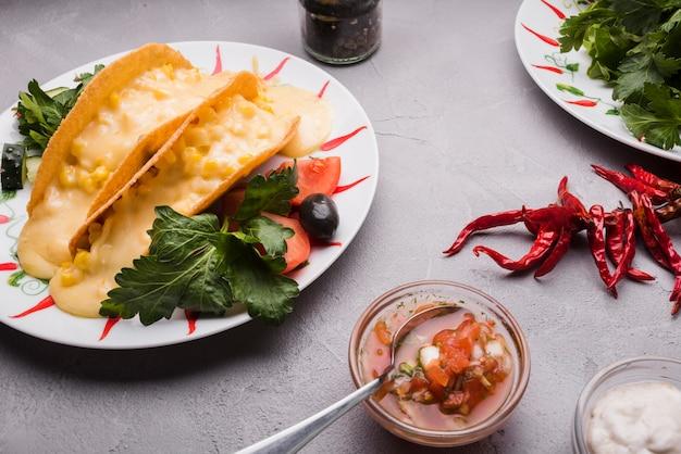 Taco unter gemüse auf teller in der nähe von chili und saucen Kostenlose Fotos