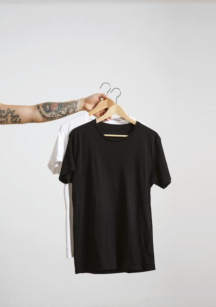 Tätowierte bikerhand hält holzhänge mit leeren schwarzen und weißen t-shirts aus hochwertiger dünner baumwolle, isoliert auf weiß Kostenlose Fotos