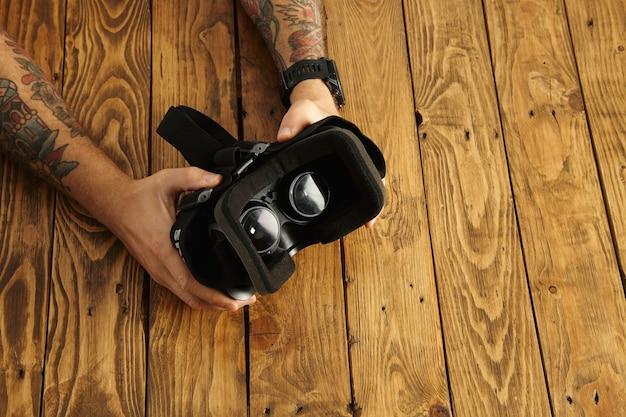 Tätowierte hände halten die brille auf den kopf und präsentieren neue technologien Kostenlose Fotos