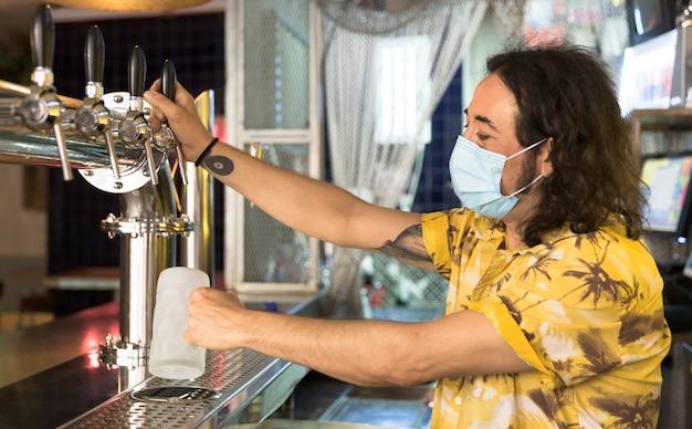 Tätowierter barmann, der einen krug bier einschenkt. Premium Fotos