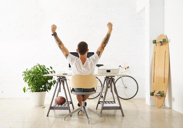 Tätowierter glücklicher freiberufler vor seinem arbeitsbereich, umgeben von seinem hobbyspielzeug longboard, vintage-fahrrad und grüner pflanze, streckte seine hand in die luft, während er pause machte Kostenlose Fotos