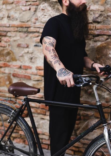 Tätowierter mann, der fahrrad gegen verwitterte backsteinmauer hält Kostenlose Fotos