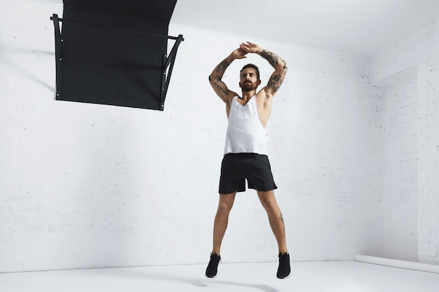 Tätowierter und muskulöser athlet, der springende wagenheber tut, die auf weißer backsteinmauer neben schwarzer zugstange isoliert werden Kostenlose Fotos
